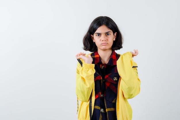 Portret van een klein meisje dat haar handpalmen uitspreidt in een geruit hemd, een jas en een weemoedig vooraanzicht kijkt