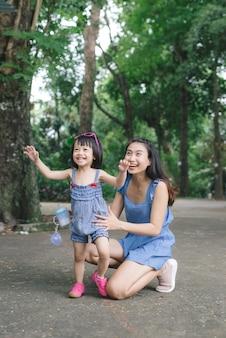 Portret van een klein meisje dat haar moeder knuffelt met de natuur en zonlicht, familieconcept