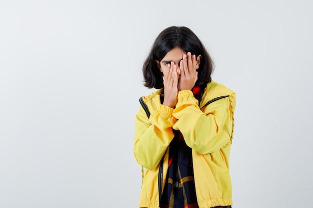 Portret van een klein meisje dat het gezicht bedekt met de handen in een geruit overhemd, een jas en een weemoedig vooraanzicht
