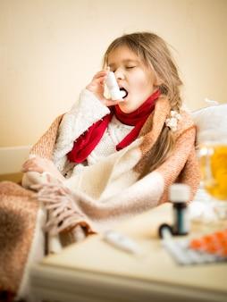 Portret van een klein meisje dat in bed zit en keelspray gebruikt