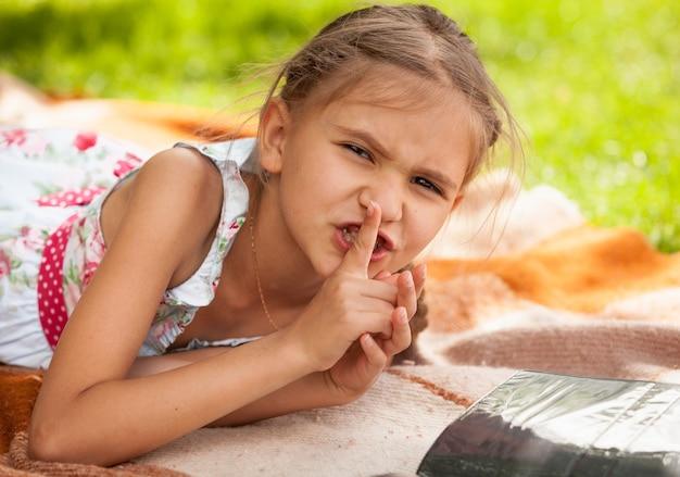 Portret van een klein meisje dat in het park ligt en vinger op de lippen houdt