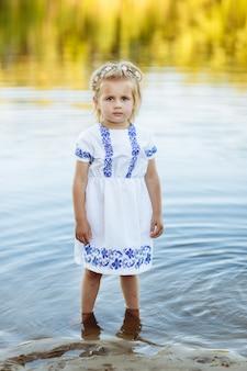 Portret van een klein meisje dat in water in een witte jurk staat. strand in de zomer.