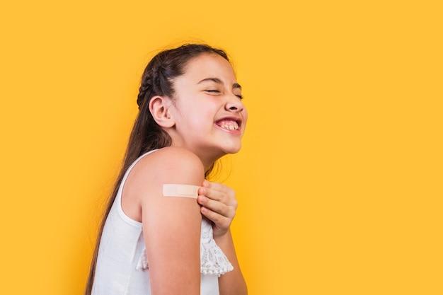 Portret van een klein meisje dat lacht na het ontvangen van een vaccinatie.