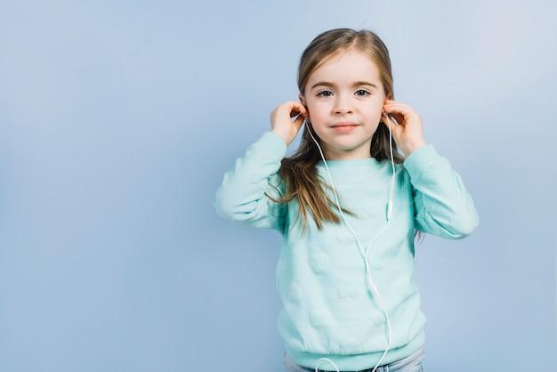 Portret van een klein meisje dat oortelefoons op haar oren zet tegen blauwe achtergrond