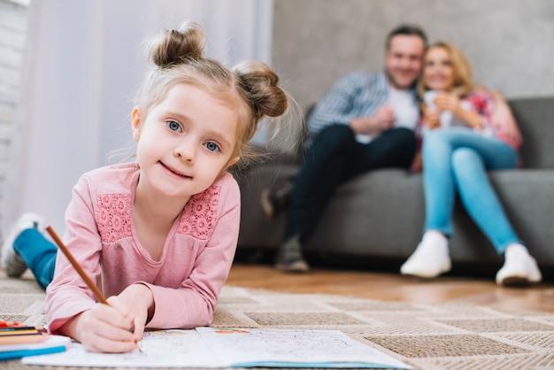 Portret van een klein meisje dat op boek met haar ouders op vage achtergrond trekt