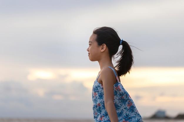 Portret van een klein meisje dat op het strand staat te genieten, kid ontspannen in de zomerzonsondergang buiten