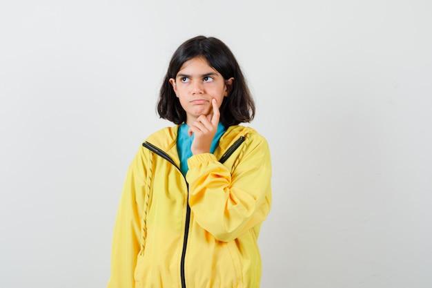 Portret van een klein meisje dat staat in denkende pose in shirt, jas en peinzend vooraanzicht
