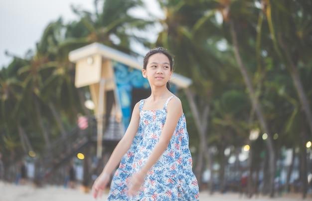 Portret van een klein meisje dat staat te genieten op het strand, kid ontspannen in de zomeravondhemel buiten