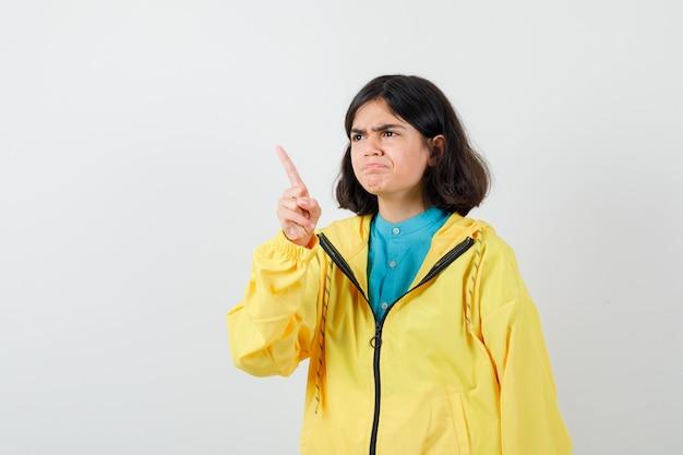 Portret van een klein meisje dat wegwijst in shirt, jas en peinzend vooraanzicht kijkt
