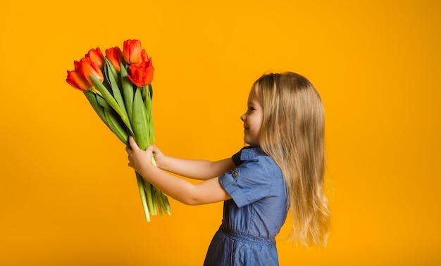 Portret van een klein meisje dat zijwaarts met een boeket rode tulpen op een gele muur met een kopie van de ruimte staat