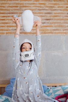 Portret van een klein meisje die het kostuum van een astronautenhelm het spelen met vliegtuig dragen