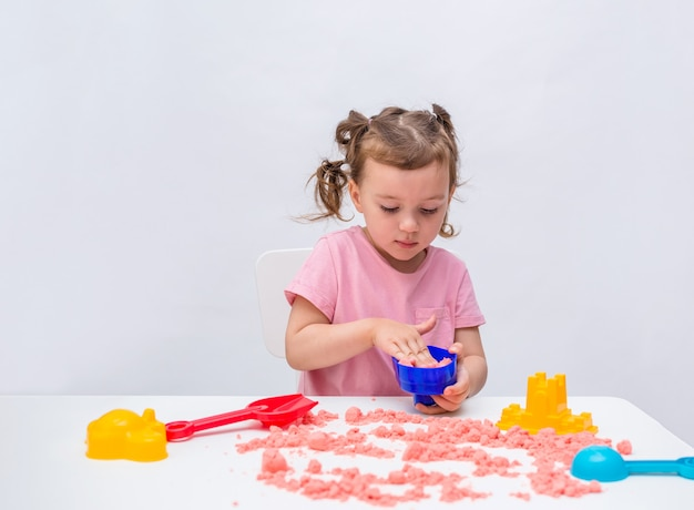 Portret van een klein meisje die met kinetisch zand op een lijst aangaande een geïsoleerd wit spelen