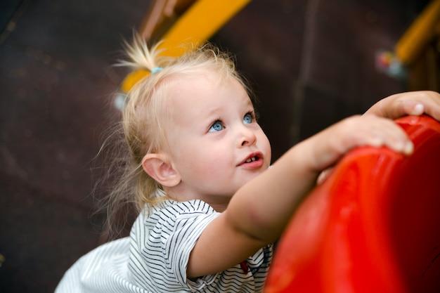 Portret van een klein meisje die op de speelplaats spelen. ruimte kopiëren.