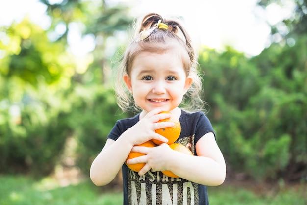 Portret van een klein meisje die rijpe sinaasappelen in handen houden