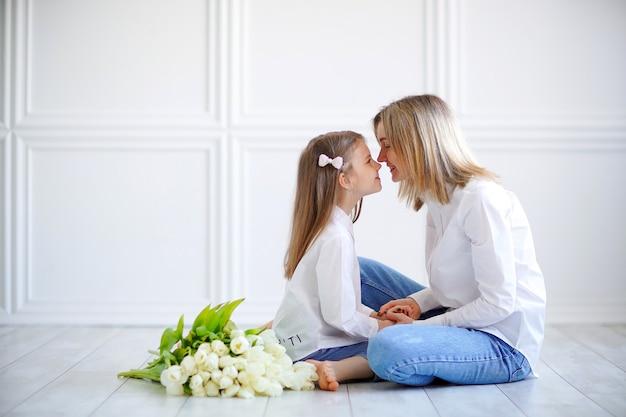 Portret van een klein meisje en liefhebbende moeder met tulpen