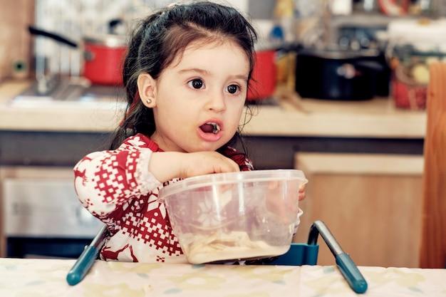 Portret van een klein meisje energetisch eten uit een kom in haar keuken
