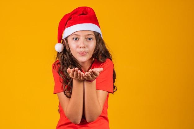 Portret van een klein meisje gekleed in kerstkleren die iets in haar handen blaast.