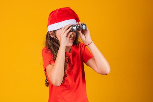 Portret van een klein meisje gekleed in kerstoutfit die door een verrekijker kijkt.