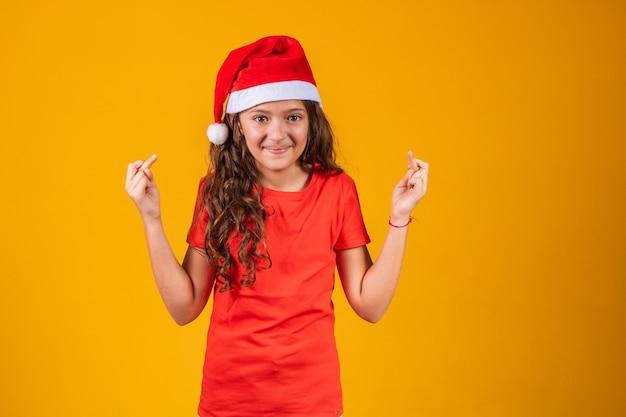 Portret van een klein meisje gekleed in kerstoutfit met gekruiste vingers die haar geluk wensen.