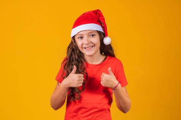 Portret van een klein meisje gekleed in kerstoutfit met haar duim omhoog.