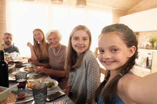 Portret van een klein meisje glimlachend en selfie portret van haar grote familie maken terwijl ze aan tafel zitten tijdens het diner thuis