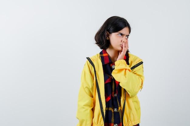 Portret van een klein meisje hand op mond in ingecheckte shirt, jas en op zoek doordachte vooraanzicht