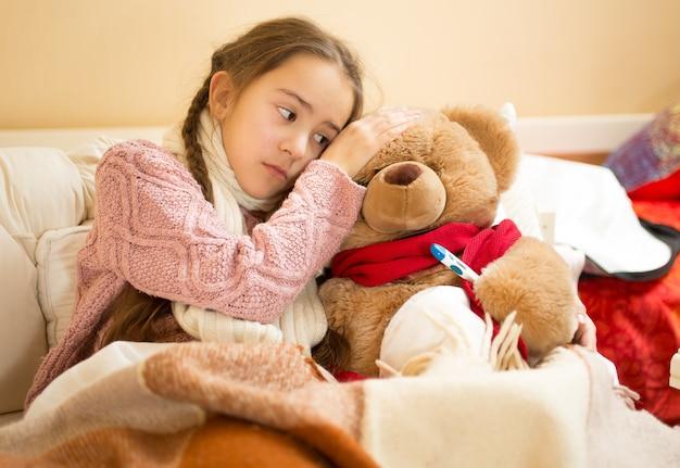 Portret van een klein meisje houdt de hand op het hoofd van de teddybeer en meet de temperatuur
