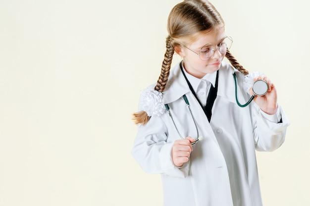 Portret van een klein meisje in de jas van een witte arts met een bril, documenten en een stethoscoop die naar de camera kijkt en glimlacht