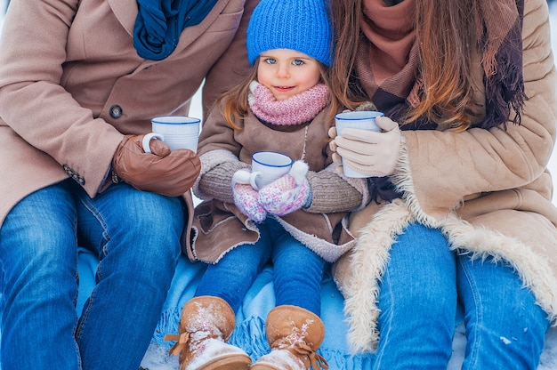 Portret van een klein meisje in een blauwe hoed en beige jas, met een kopje, met haar ouders, close-up