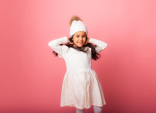 Portret van een klein meisje in een gebreide witte wintermuts en witte jurk op een roze achtergrond