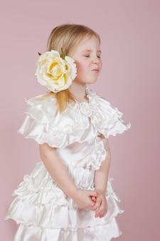 Portret van een klein meisje in een jurk met bloem