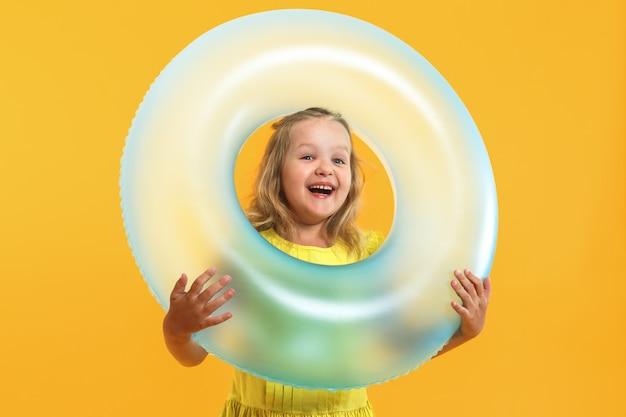 Portret van een klein meisje in een jurk met een zwemband.