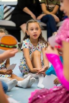 Portret van een klein meisje in een jurk zittend op de vloer, omringd door kinderen aandachtig luisteren