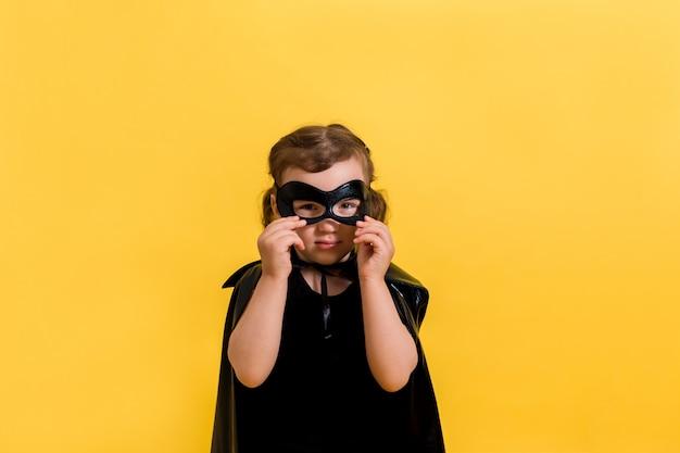 Portret van een klein meisje in een pak met een zwart masker