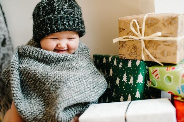 Portret van een klein meisje in een warme gebreide muts met een sjaal, zit in de kamer met geschenken. feestelijk verjaardagsconcept. baby op de foto. zuigeling. vrouwendag. prettige kerstdagen, fijne feestdagen.