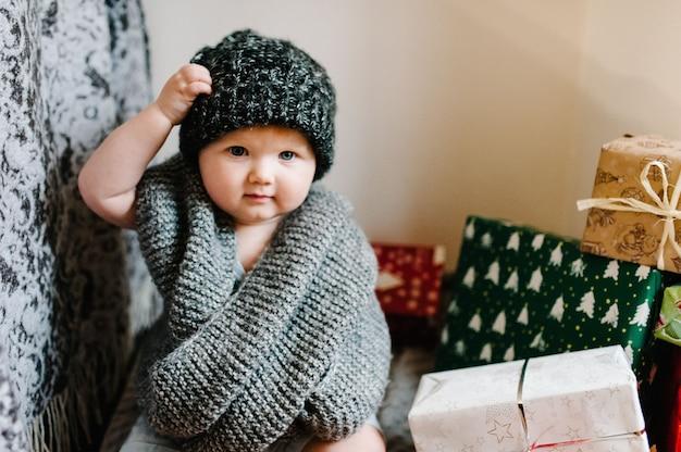 Portret van een klein meisje in een warme gebreide sjaal, hoed verwijdert, zit in de kamer met geschenken. feestelijk verjaardagsconcept. baby op de foto. zuigeling. vrouwendag. prettige kerstdagen, fijne feestdagen.