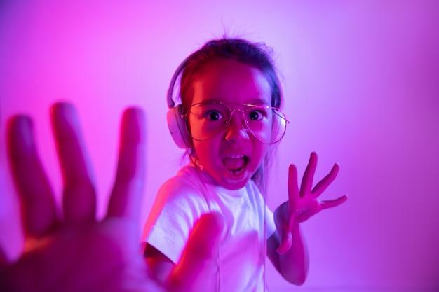 Portret van een klein meisje in koptelefoon op paarse kleurovergang muur in neonlicht