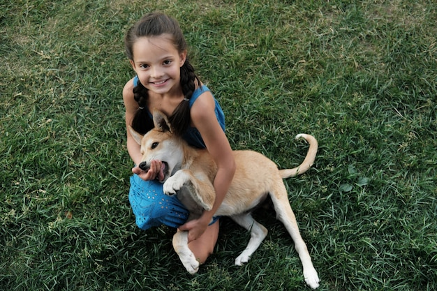 Portret van een klein meisje lachend zittend op het gras en spelen met haar hond buiten