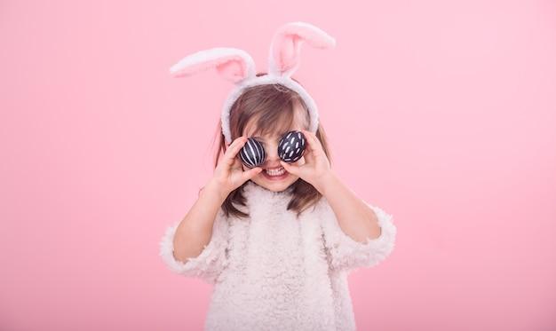 Portret van een klein meisje met bunny oren en paaseieren