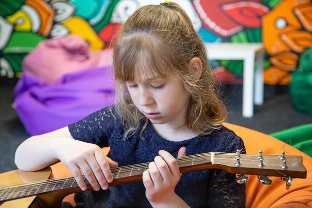 Portret van een klein meisje met een akoestische gitaar in haar handen