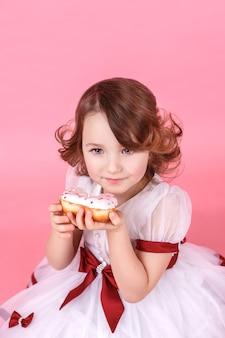 Portret van een klein meisje met een donut in haar handen op roze