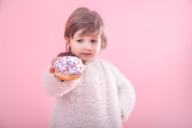 Portret van een klein meisje met een donut in haar handen