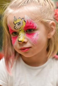 Portret van een klein meisje met een eenhoornpatroon op haar gezicht