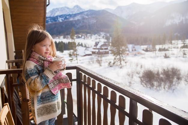 Portret van een klein meisje met een kopje thee op bergen, zakopane, koscielisko.