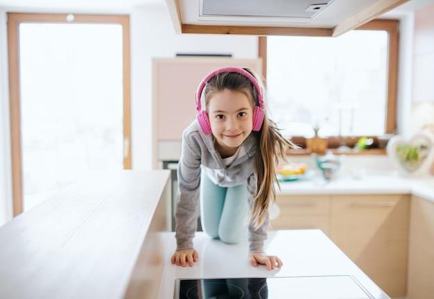 Portret van een klein meisje met een koptelefoon binnenshuis op het aanrecht thuis, kijkend naar de camera.