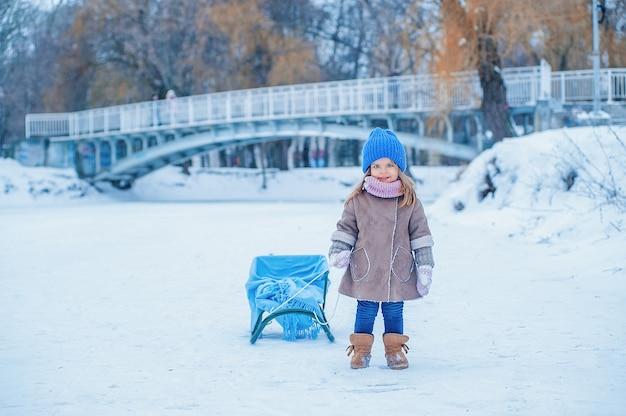 Portret van een klein meisje met een slee op een achtergrond van sneeuw in het park
