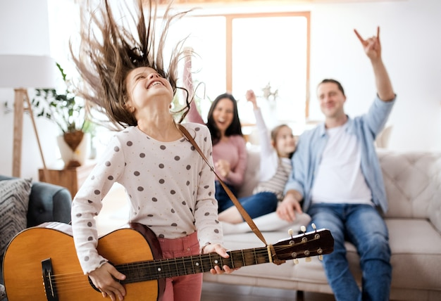 Portret van een klein meisje met familie binnenshuis, plezier maken met gitaar.
