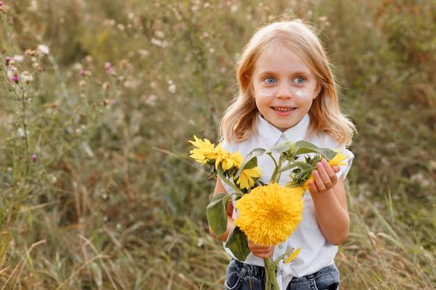 Portret van een klein meisje met gele bloemen in de zomer op een wandeling. vrije ruimte voor tekst