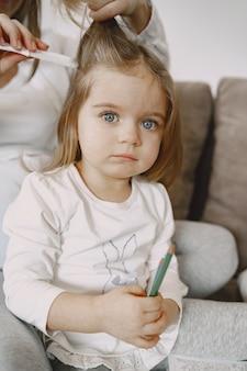Portret van een klein meisje met haar moeder die haar haar bindt.