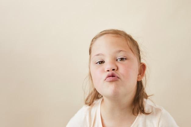 Portret van een klein meisje met het syndroom van down die de kus verzenden naar camera geïsoleerd op een witte achtergrond
